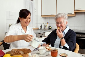 a geriatric nurse helps elderly woman at breakfast. elder care of seniors